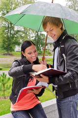 Two students under umbrella in the park