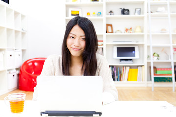 a young asian woman using laptop computer