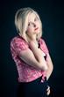 Portrait of blonde teenager girl on black background.