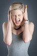 Portrait of screaming desperate blonde teenager girl on dark bac
