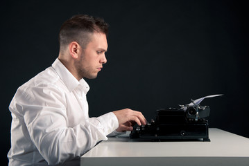 Young man writing with an old typewriter. Retro image