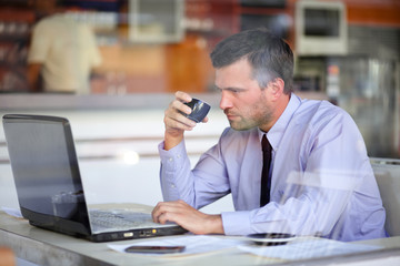 Authentic image of a businessman drinking coffee while working i