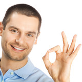 Cheerful man showing okay sign, over white