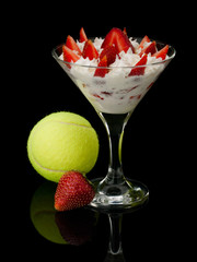 Strawberry with cream and a tennis ball.