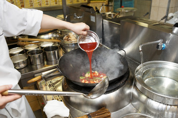 Chef is pouring sour sauce in wok