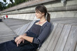 lonely woman sitting by the river on wooden embankment