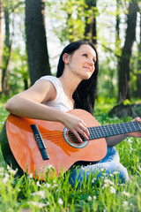 Young woman playing the guitar outdoors