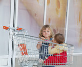 two children - girl and baby - in shopping cart in supermarket