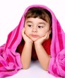 Little girl under pink blanket, on white background