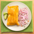 Peruvian tamale made of corn and chicken with salsa criolla