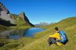 Wanderer rastet mit Blick auf Bergsee