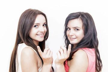 junge, hübsche Frauen zeigen auf Dich
