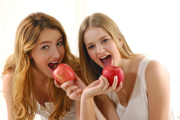 healthy girls eating apples over a white