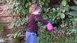 enfant arosant les fleurs