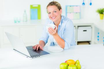 frau arbeitet am laptop in der küche