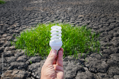 energy saving lamp in hand over green grass and cracked earth
