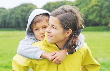Mutter trägt Sohn auf dem Rücken