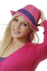 Hübsche blonde Frau mit pinkem Hut