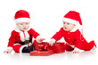 two funny small kids in Santa Claus clothes with gift box