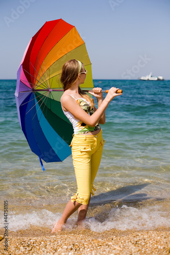 Teenage girl carrying iridiscent umbrella