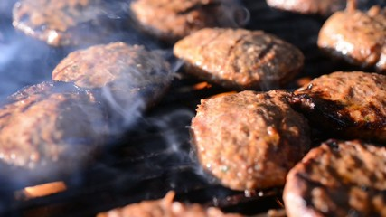 hamburgers cooking on a barbeque grill with flames and smoke