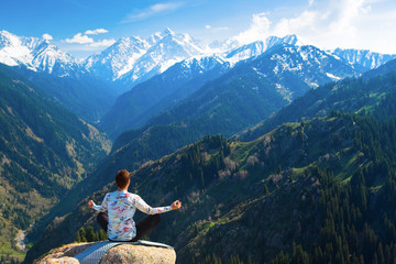 Young man meditating on top of the mountain
