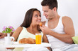 Cheerful couple having breakfast in bed