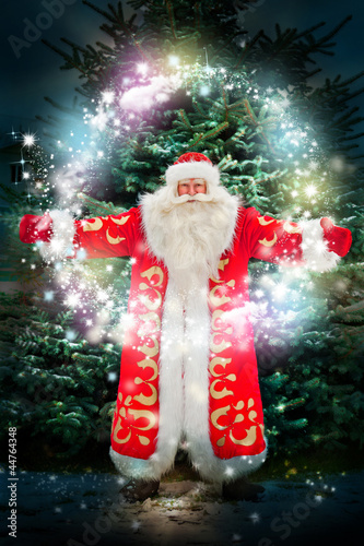 Portrait of Santa Claus conjuring against christmas tree