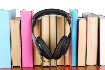 Headphones on books on wooden table on white background