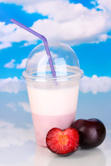 Delicious milk shake with fruit on table on sky background
