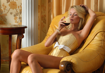 Beautiful undressed woman with glasss o red wine in luxury inter