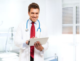 Handsome doctor using a tablet