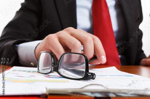 Businessman laying down his eyeglasses