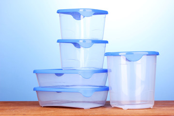 Plastic containers for food on wooden table on blue background