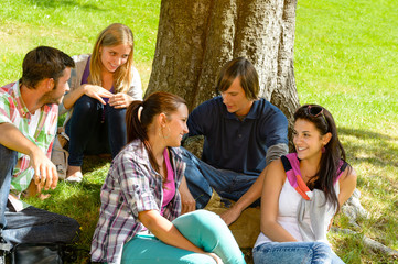 Students sitting in park talking smiling teens