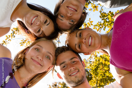 Teens in a circle smiling in park