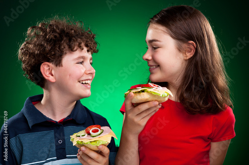 Kids eating big sandwiches