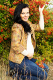 Portrait of beautiful pregnant woman walking in autumn park