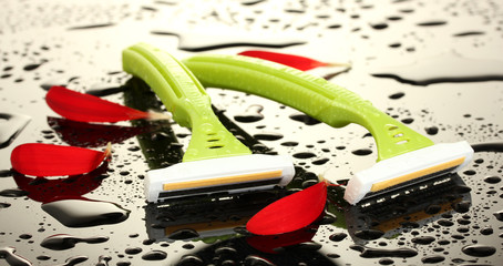 woman safety shavers with drops and petals on grey backgroud.