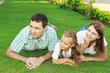 Постер, плакат: Молодая семья смотрит в сторону лежа на газоне