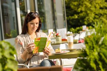 Woman looking at menu cafe bar terrace