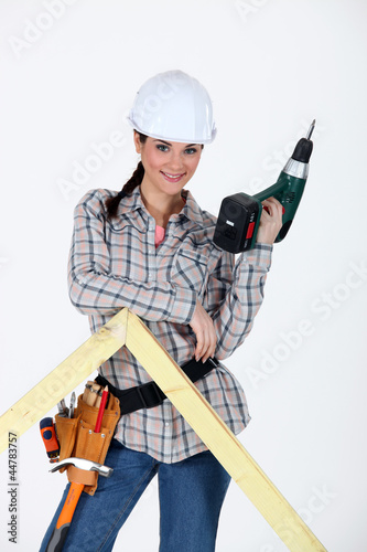 Woman drilling hole in wooden frame