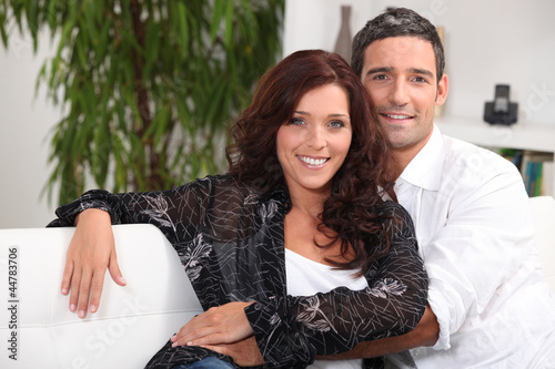 Couple embracing on white sofa