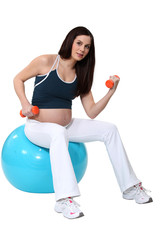 portrait of cute pregnant brunette doing exercise