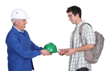 Builder handing hard-hat to young worker