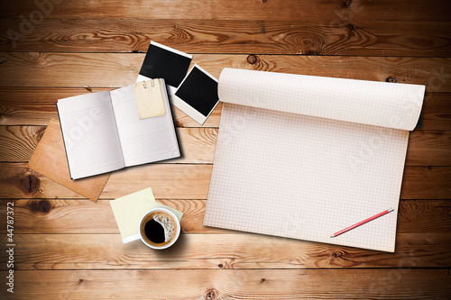 Workspace with coffee cup, instant photos, note paper and notebo