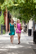 Female Friends Walking On Sidewalk
