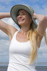 Frau mit Sommerhut am Strand