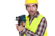 A man holding a drill with a weird facial expression.