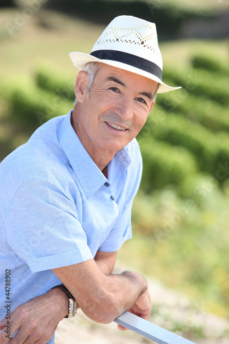 Old man leaning against railing